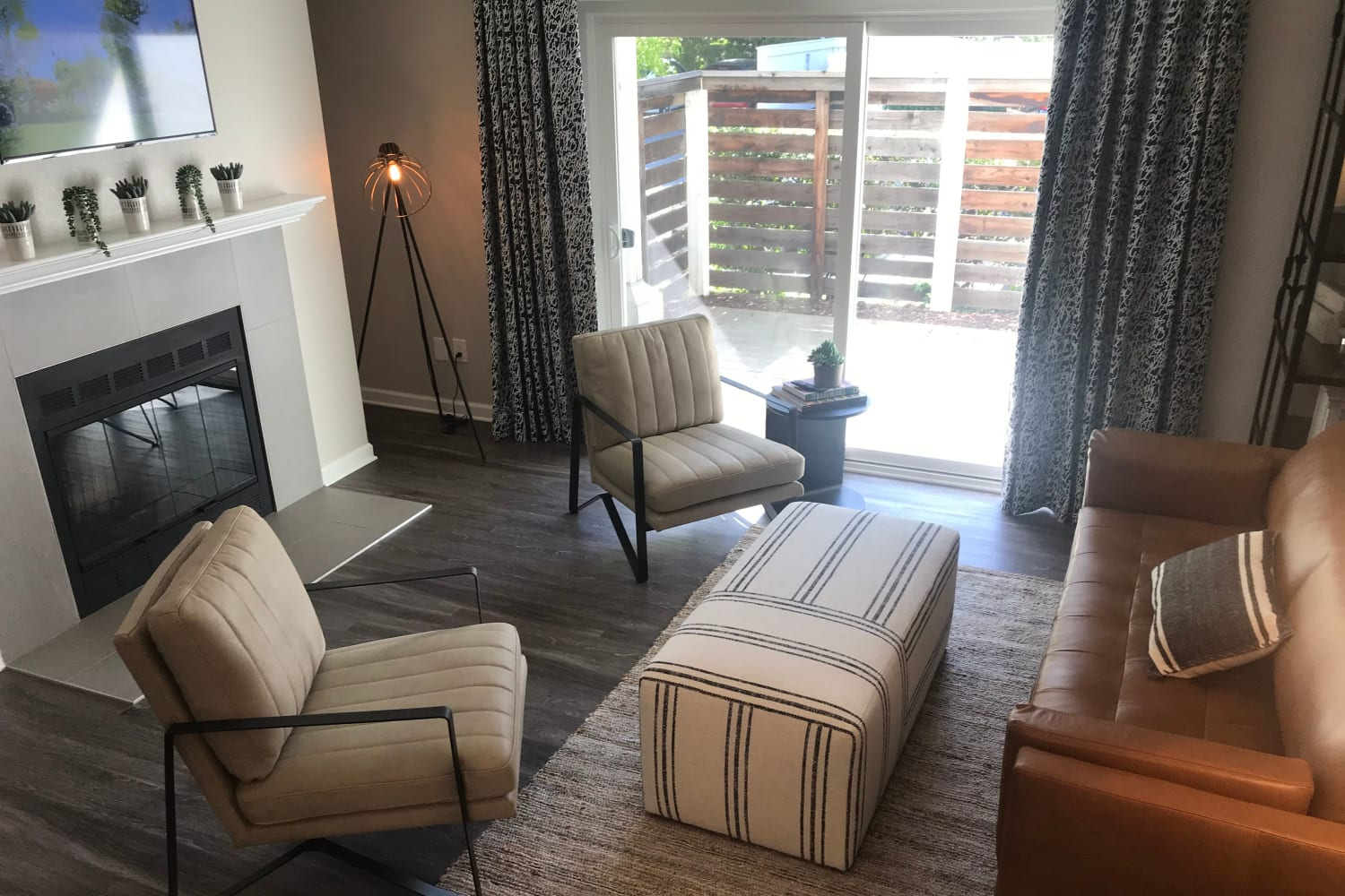 Living rooms with hardwood floors, a fireplace and a private patio at Cotton Wood Apartments in Dublin, California
