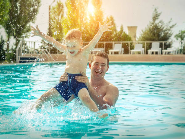 Father and son playing in the pool at TerraLane at Canyon Trails in Goodyear, Arizona