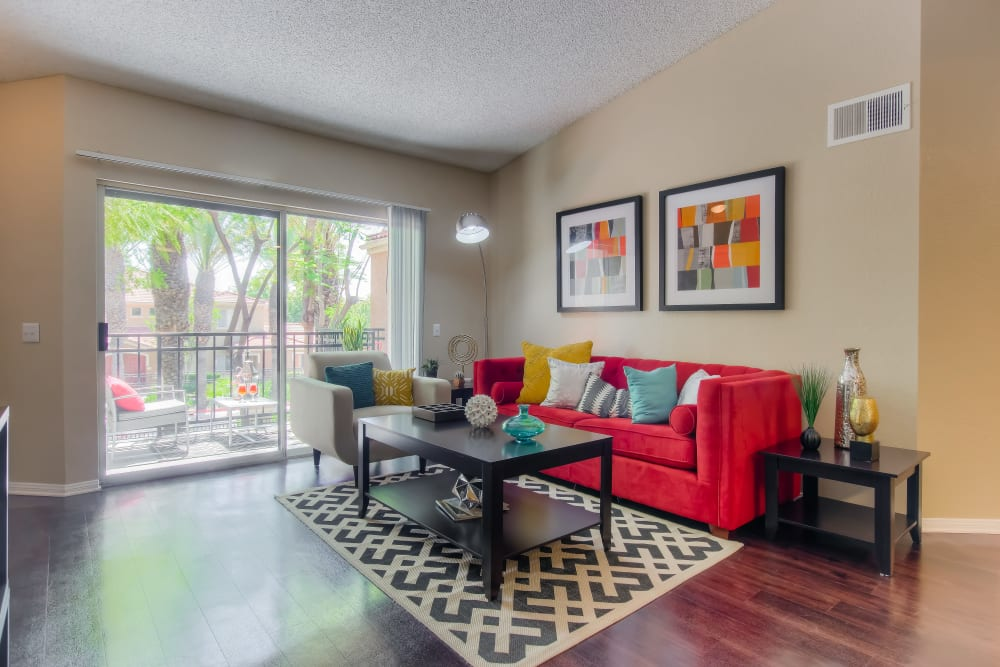 A living room complete with a private patio at Tuscany Village Apartments in Ontario, California