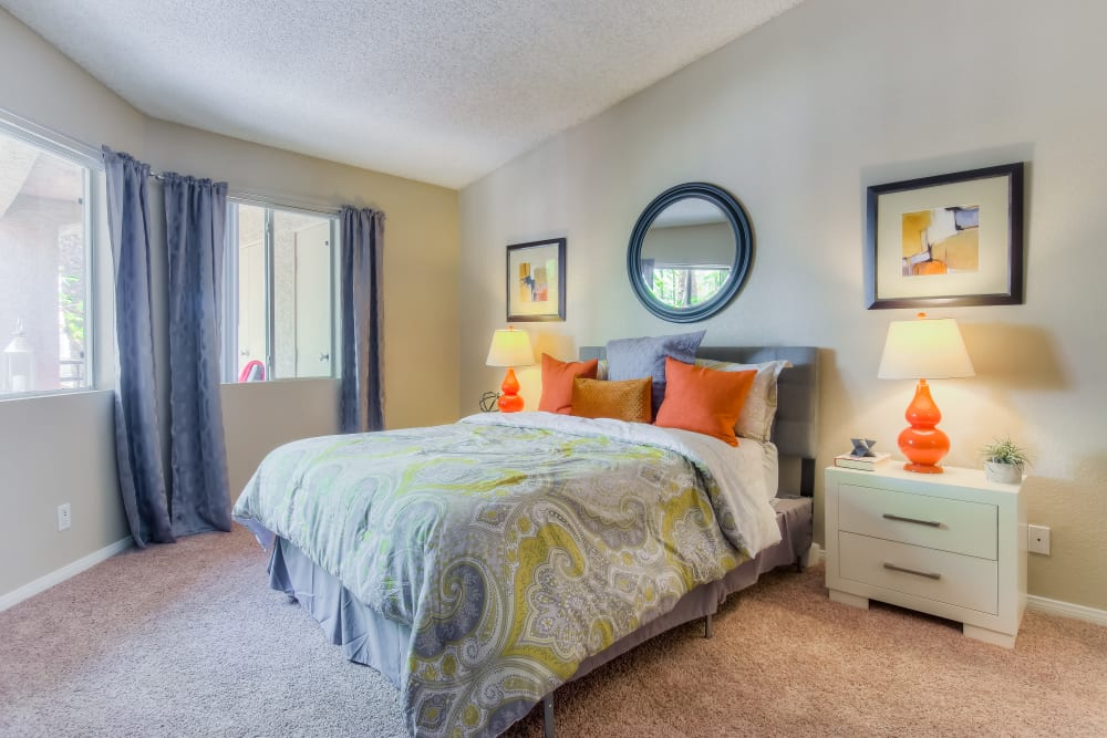 Decorated master bedroom with large windows at Tuscany Village Apartments in Ontario, California