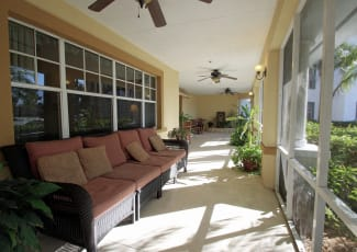 A porch with plenty of seating at Sunset Lake Village Senior Living in Venice, FL