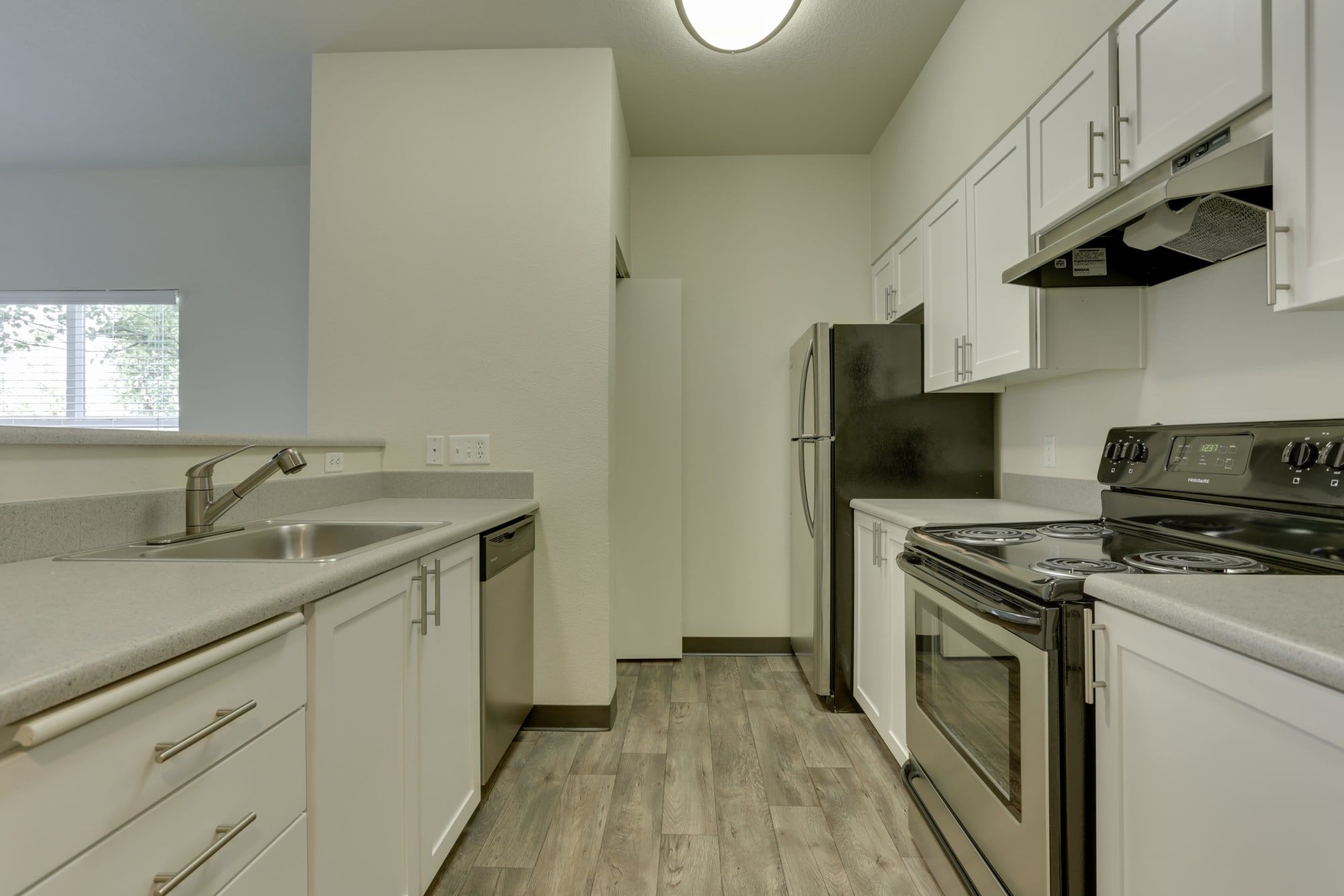 white renovated kitchen view with stainless steel appliances at The Landings at Morrison Apartments