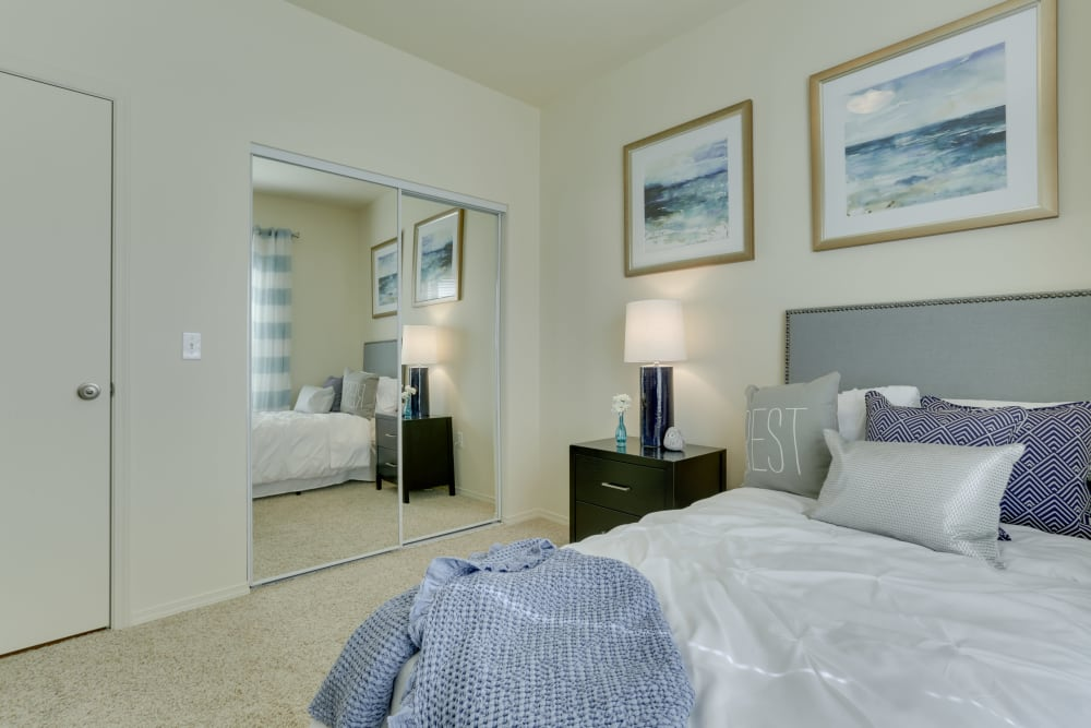 Master bedroom with a large mirrored closet door at The Landings at Morrison Apartments in Gresham, Oregon