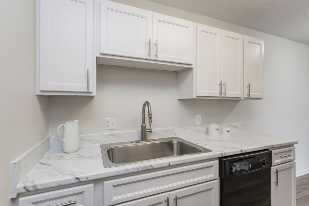 Stainless-steel sink and white tile countertops in the kitchen of an apartment home at Audubon Park in Nashville, Tennessee
