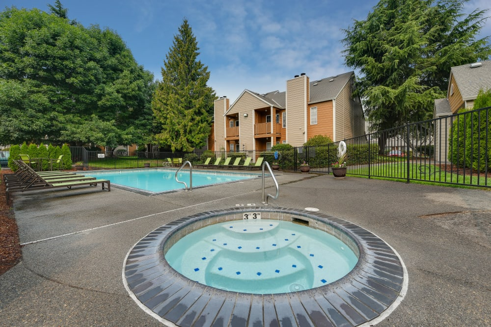 Beautiful resort-style hot tub and swimming pool with a lush backdrop at Carriage House Apartments in Vancouver, Washington