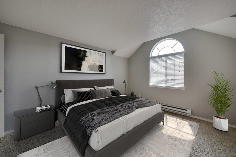 Decorated master bedroom with a large window at Walnut Grove Landing Apartments in Vancouver, Washington