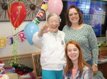 senior resident and family celebrating