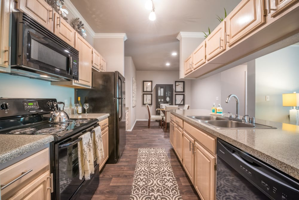 Beautiful cabinetry, kitchen sink and dining area view at 23Hundred at Ridgeview in Plano, Texas