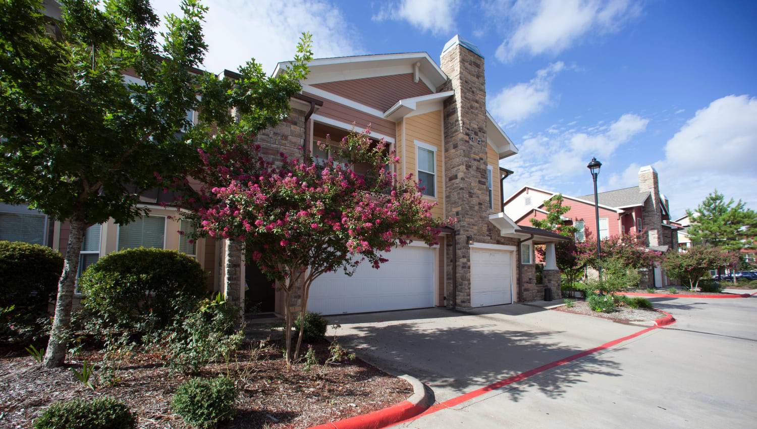 Well-maintained landscaping outside townhomes at Olympus Katy Ranch in Katy, Texas