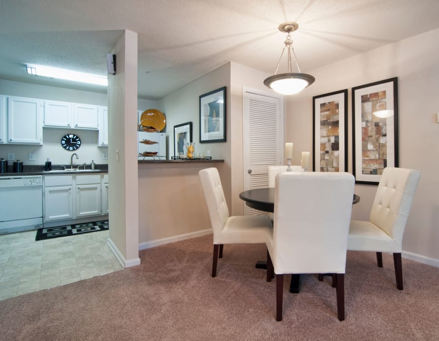 Well-decorated dining area with a view of the kitchen over the breakfast bar in a model at Bellingham Apartment Homes in Marietta, Georgia