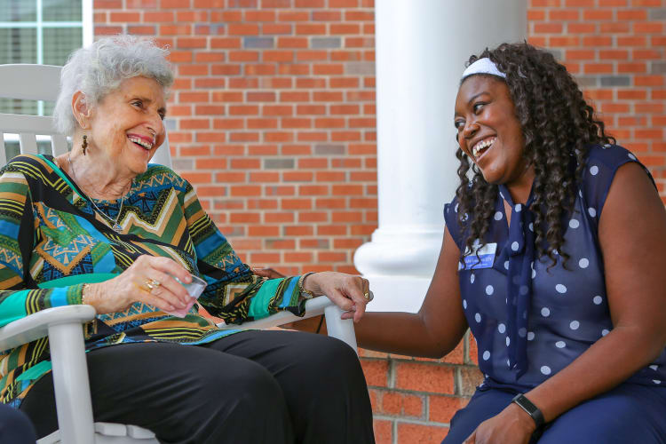 A resident holding hands with her daughter outside at The Harmony Collection at Hanover - Assisted Living & Memory Care in Mechanicsville, Virginia