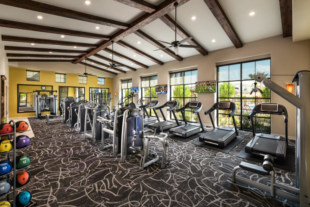 24/7 fitness center with individual workout stations and TVs at San Posada in Mesa, Arizona
