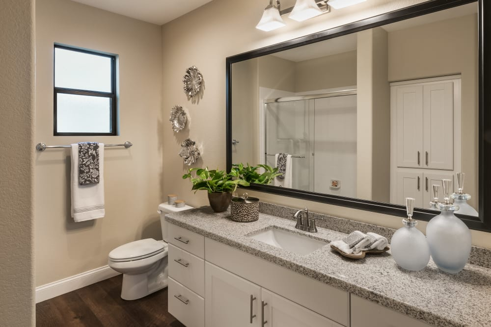 Bathroom with large vanity mirror and granite countertop in model home at San Villante in Mesa, Arizona