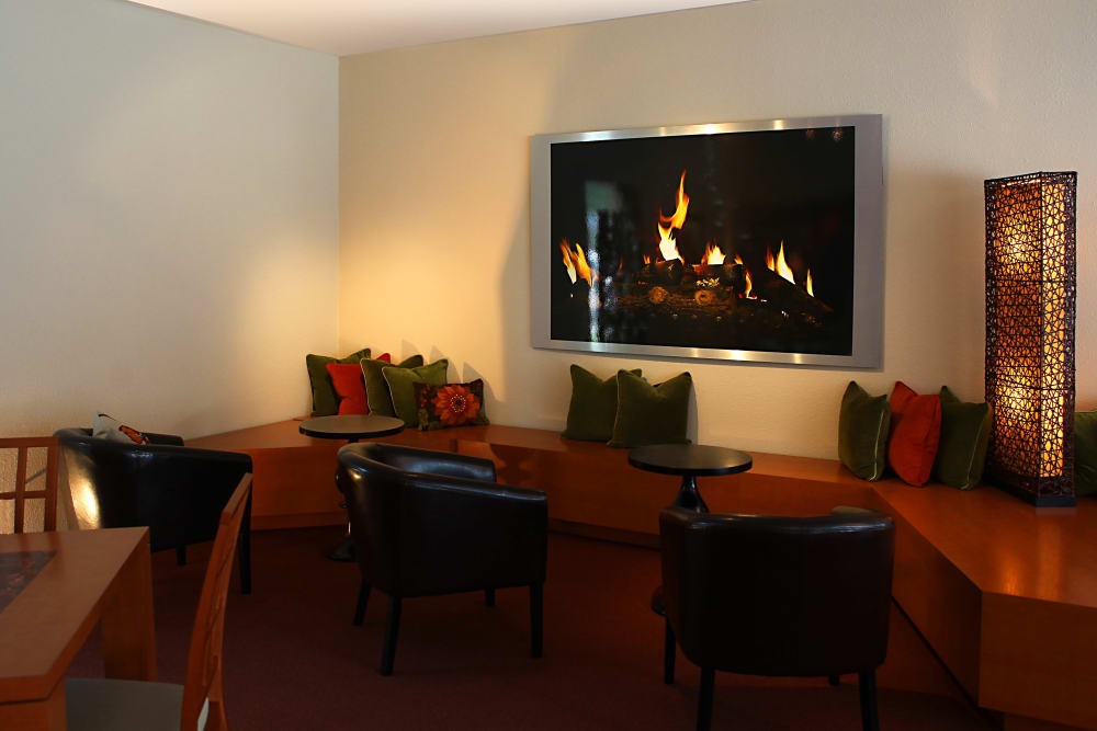 Comfortable seating in front of the TV in the clubhouse at Kensington Manor Apartments in Farmington, Michigan