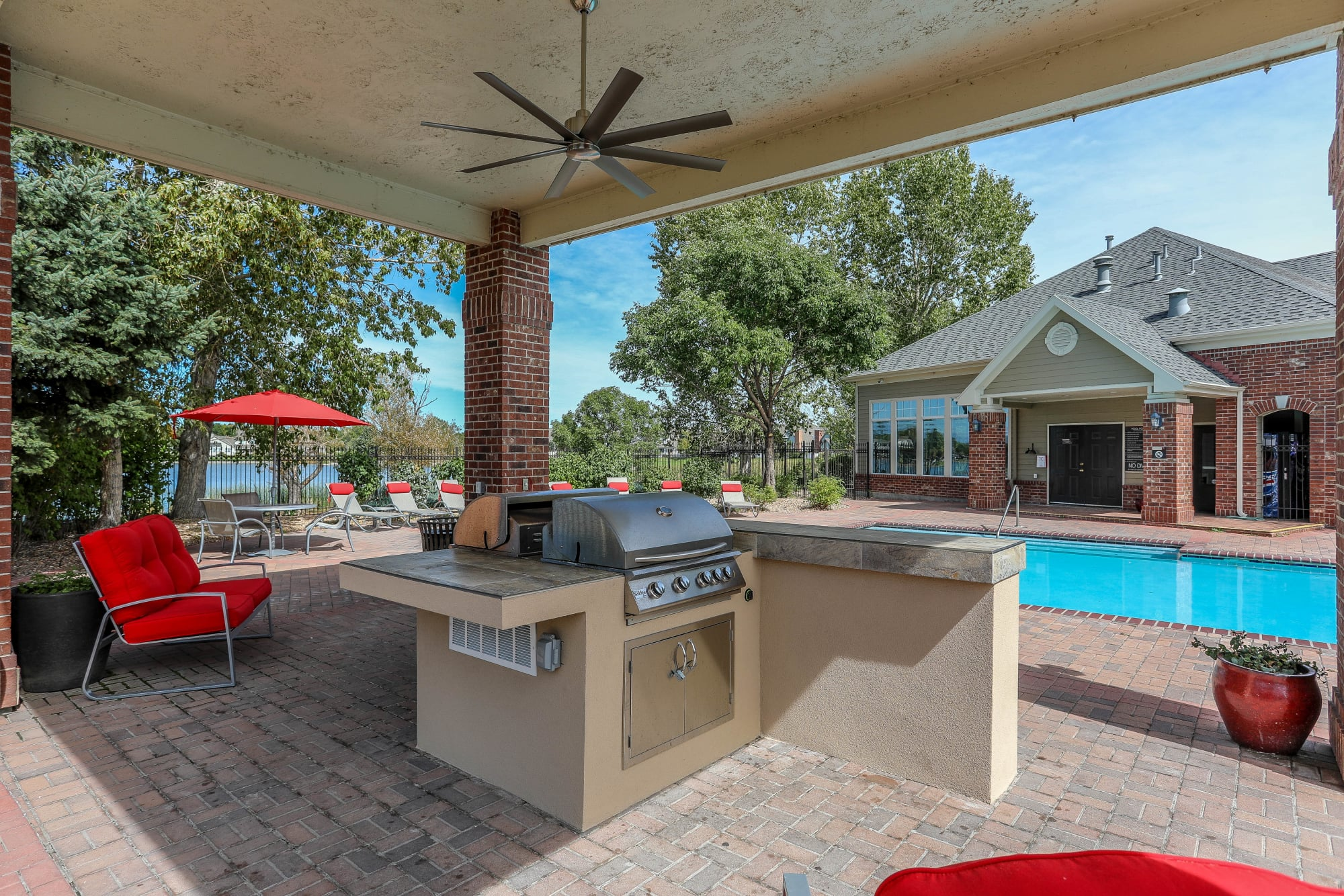 Poolside covered BBQ area with bar top seating at Promenade at Hunter's Glen Apartments in Thornton, Colorado