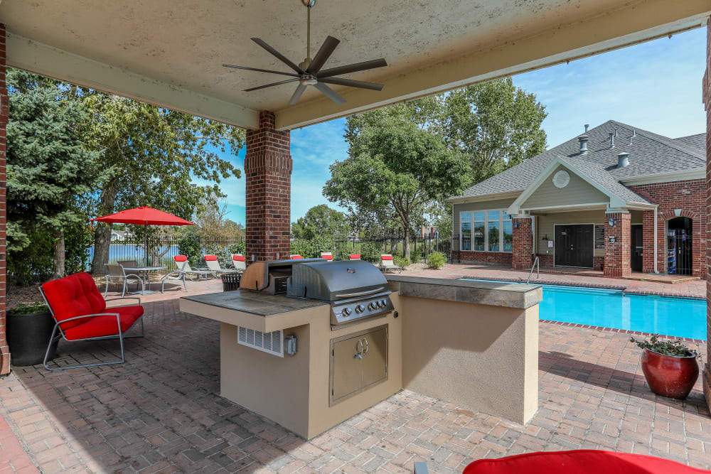 Poolside covered grilling area with bar top seating at Promenade at Hunter's Glen Apartments in Thornton, Colorado