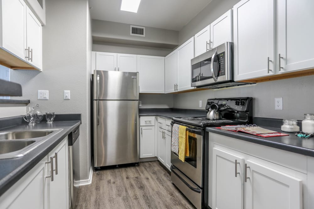 Kitchen with wood-style flooring at Promenade at Hunter's Glen Apartments in Thornton, Colorado