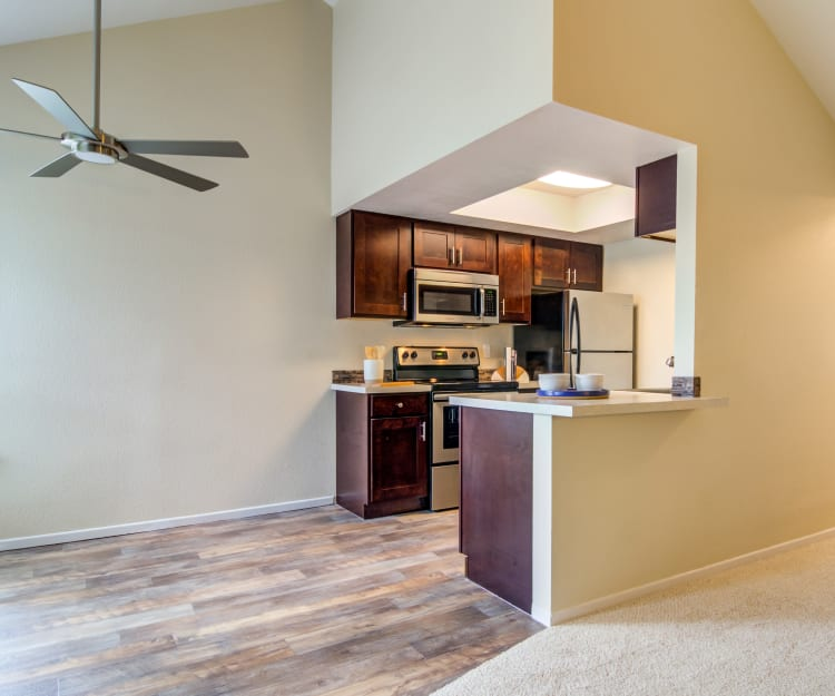 Dining area with a vaulted ceiling and a ceiling fan next to the modern kitchen in a model home at Sofi Lake Oswego in Lake Oswego, Oregon