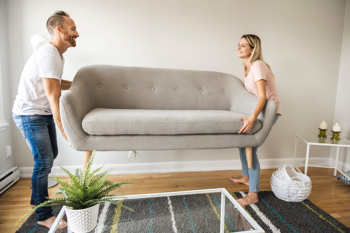 Couple moving couch into storage at Devon Self Storage in Grand Rapids, Michigan