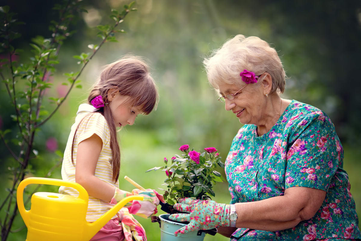 A resident and a small child planting flowers at Keystone Place at Newbury Brook in Torrington, Connecticut