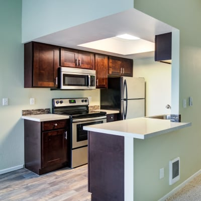 Modern kitchen with granite countertops and a breakfast bar in a model home at Sofi Lake Oswego in Lake Oswego, Oregon