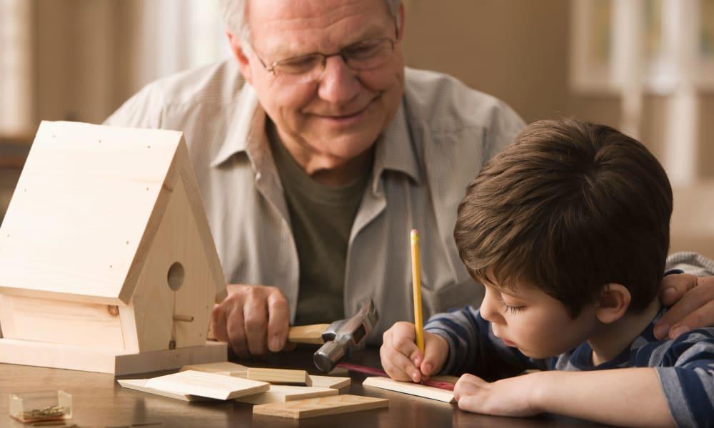 A resident and a boy building a birdhouse at Amaran Senior Living in Albuquerque, New Mexico.