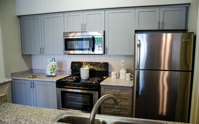 Grey cabinetry in a kitchen with stainless steel appliances at Wildreed Apartments in Everett, Washington