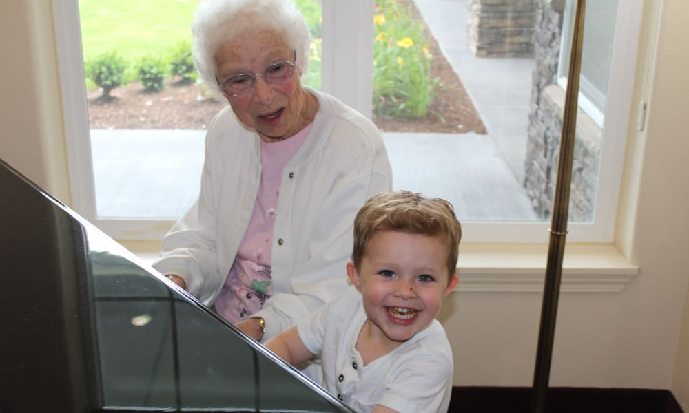 A resident of Carolina Estates playing the piano with a family member