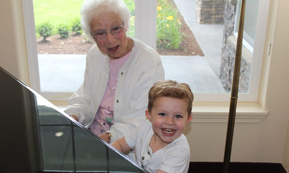 Resident playing the piano with her grandson at Alexis Estates Gracious Retirement Living in Allen, Texas