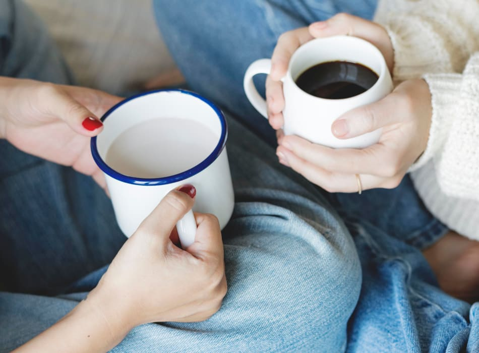 Residents having some warm cups of coffee while sitting on the floor at Sofi Lyndhurst in Lyndhurst, New Jersey