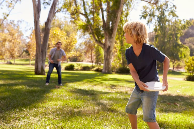 Father and son throwing frisbee in park together near San Miguel del Bosque in Albuquerque, New Mexico