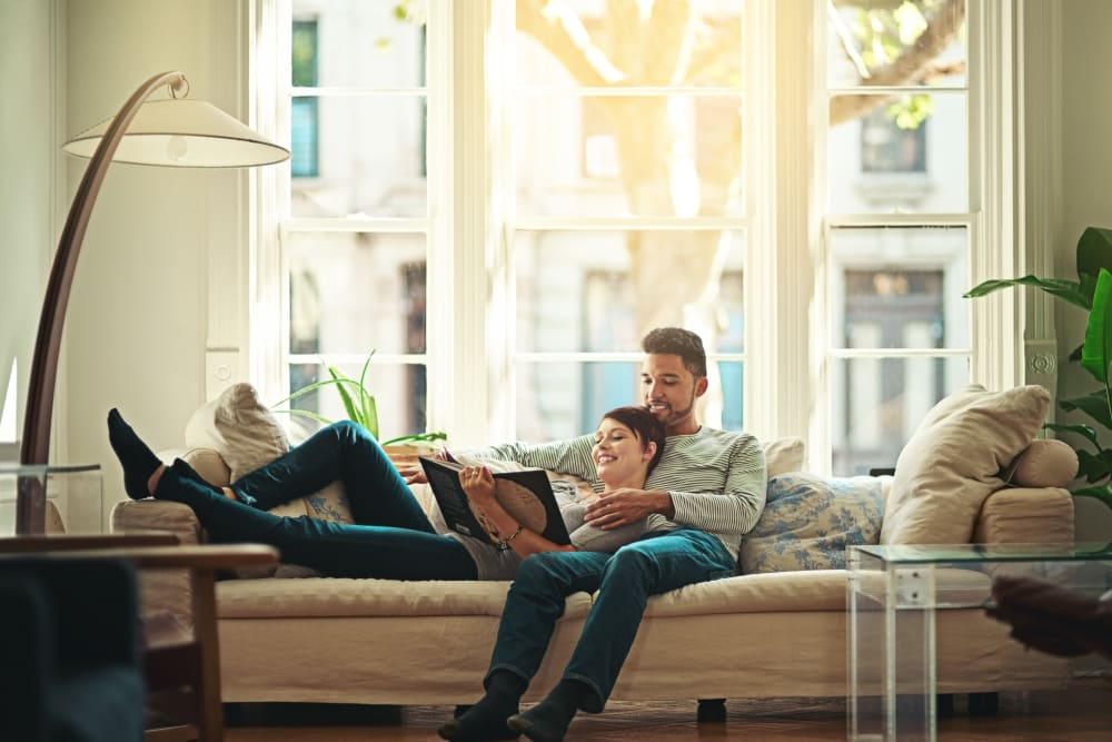 Couple relaxing on the couch in their new apartment home at The Reserve at Gilbert Towne Centre in Gilbert, Arizona