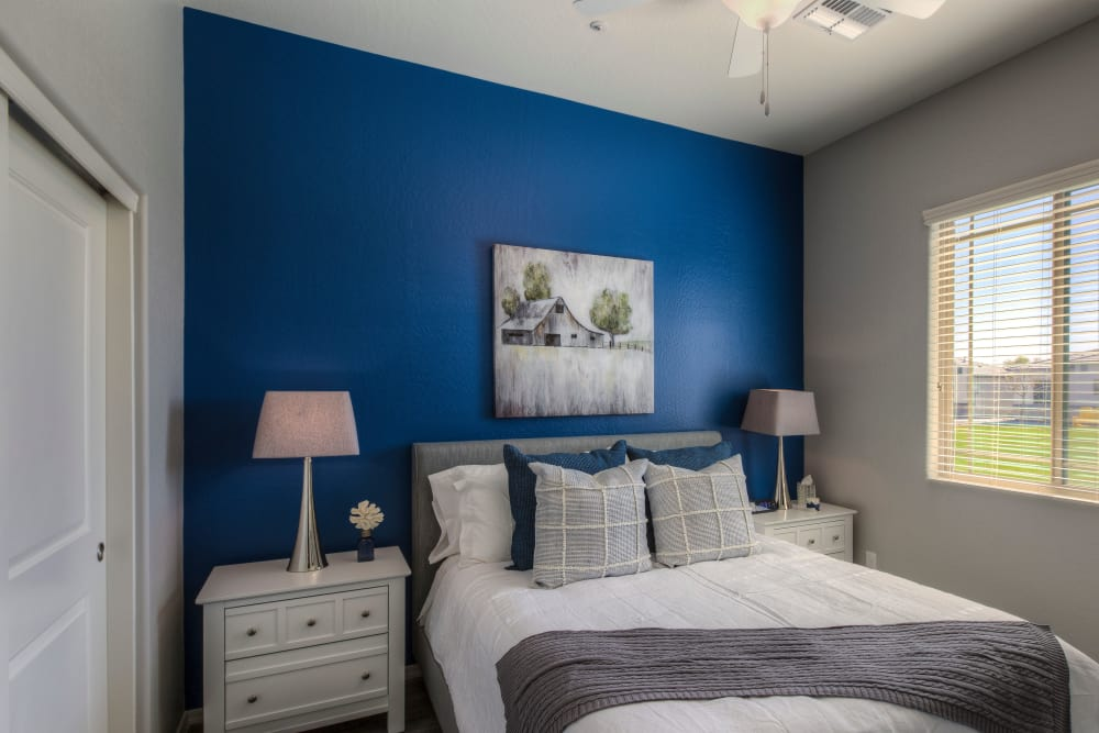 Large master bedroom with ceiling fan and beautiful furnishings in model home at San Palmas in Chandler, Arizona