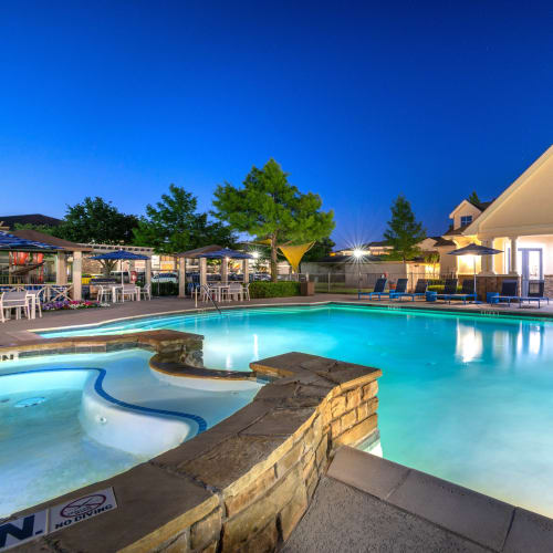 Resort-style swimming pool at dusk at Olympus Stone Glen in Keller, Texas