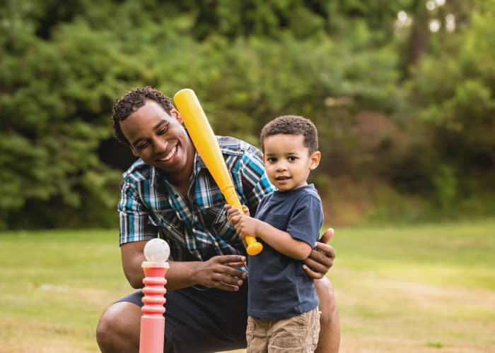 Father and son playing tee ball near Greenwoods in Brockton, Massachusetts