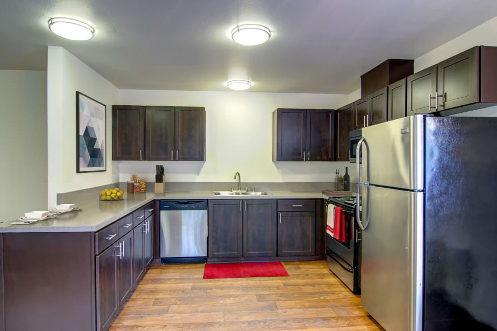 Kitchen with wood-style flooring at The Addison Apartments in Vancouver, Washington