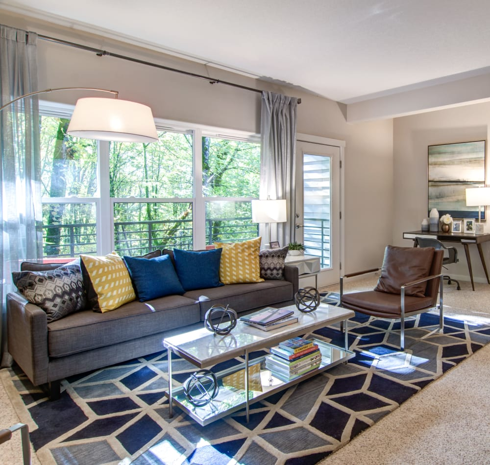 Open-concept layout with plush carpeting and modern furnishings in a model home's living area at Sofi at Forest Heights in Portland, Oregon