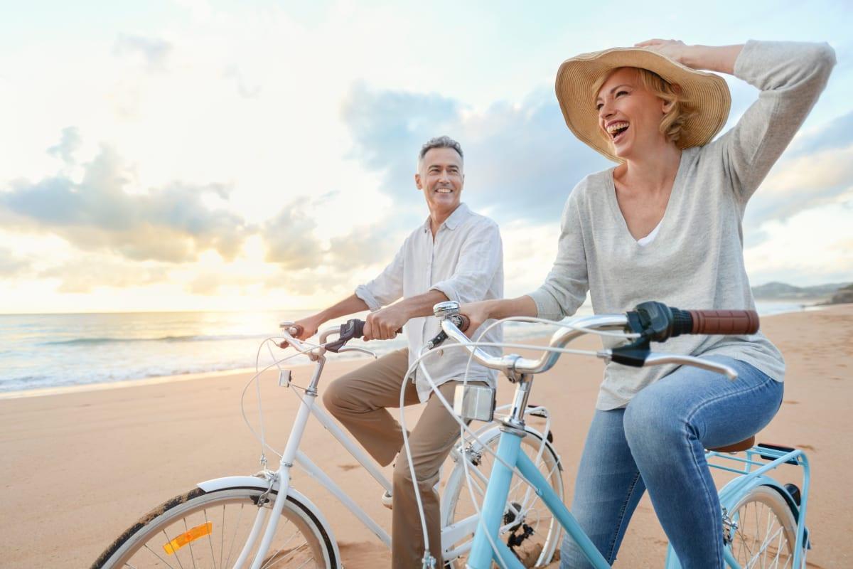 Resident couple riding bikes on the beach near The Pointe at Siena Ridge in Davenport, Florida