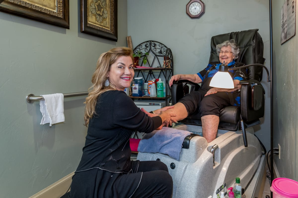 A resident enjoying a pedicure at Watercrest at Bryan in Bryan, Texas