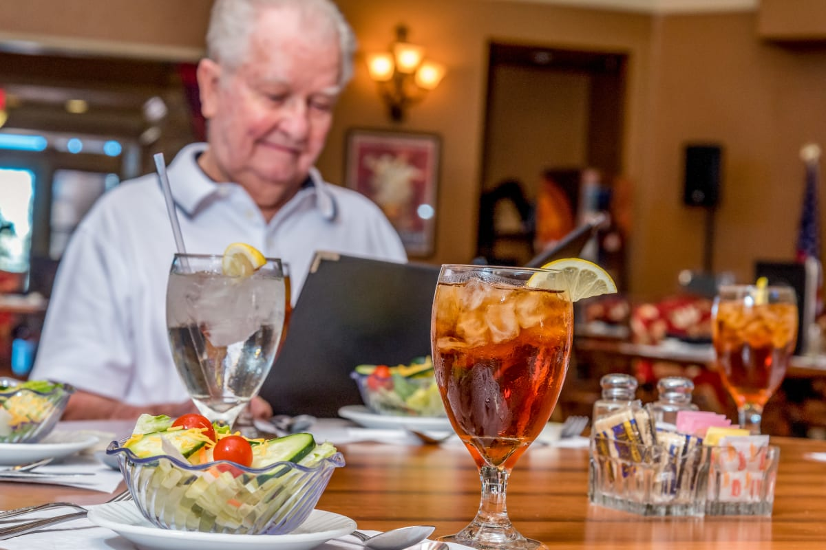 Resident choosing from a menu at Watermere at Woodland Lakes in Conroe, Texas