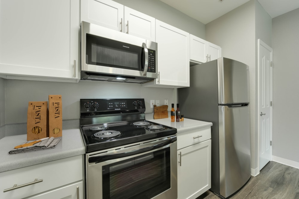 Kitchen with wood-style flooring and stainless steel appliances at The Grove at Orenco Station in Hillsboro, Oregon