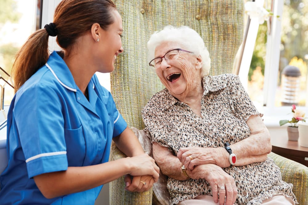 Caregiver laughing with senior woman
