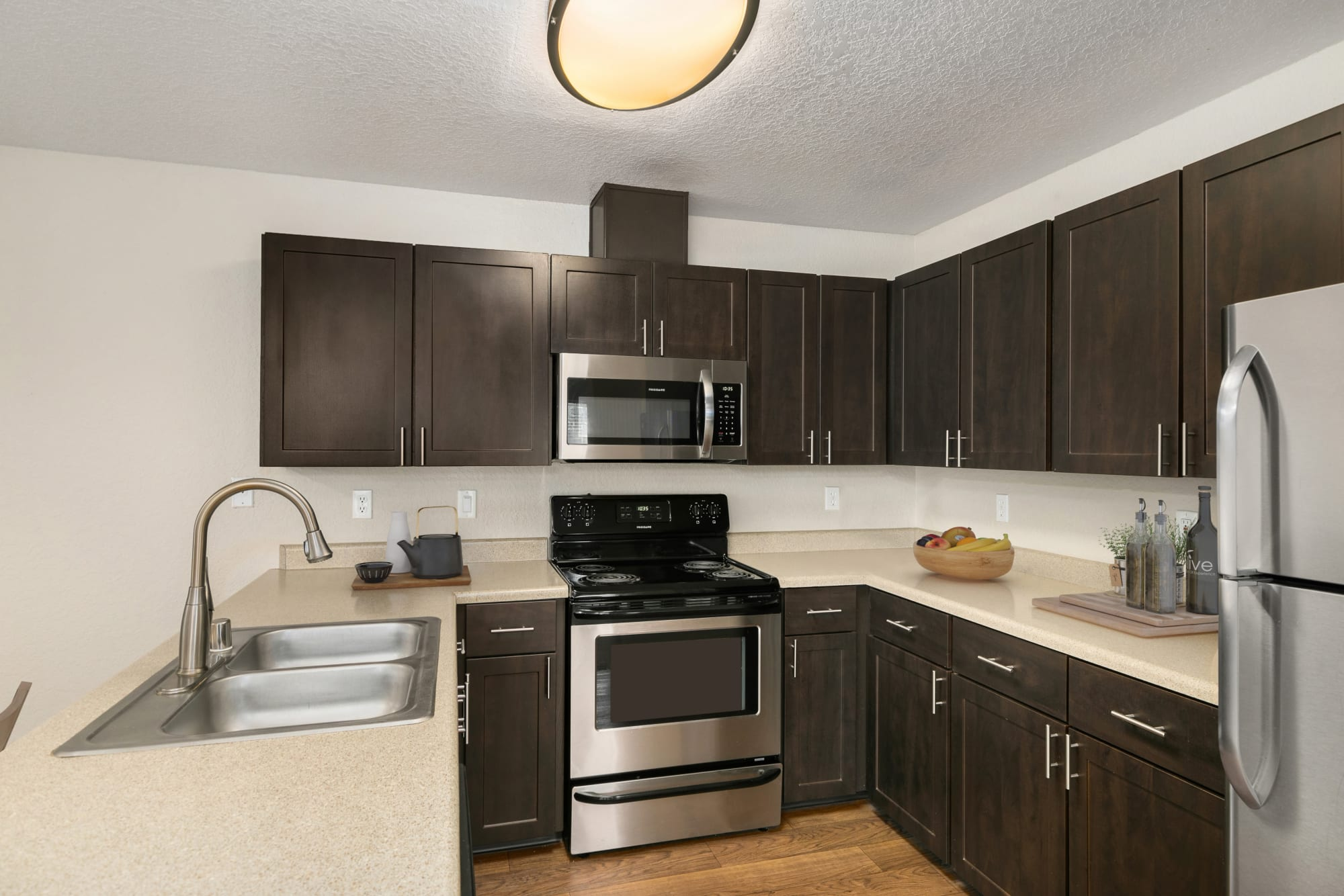 Renovated kitchen with espresso cabinetry at Carriage Park Apartments in Vancouver, Washington
