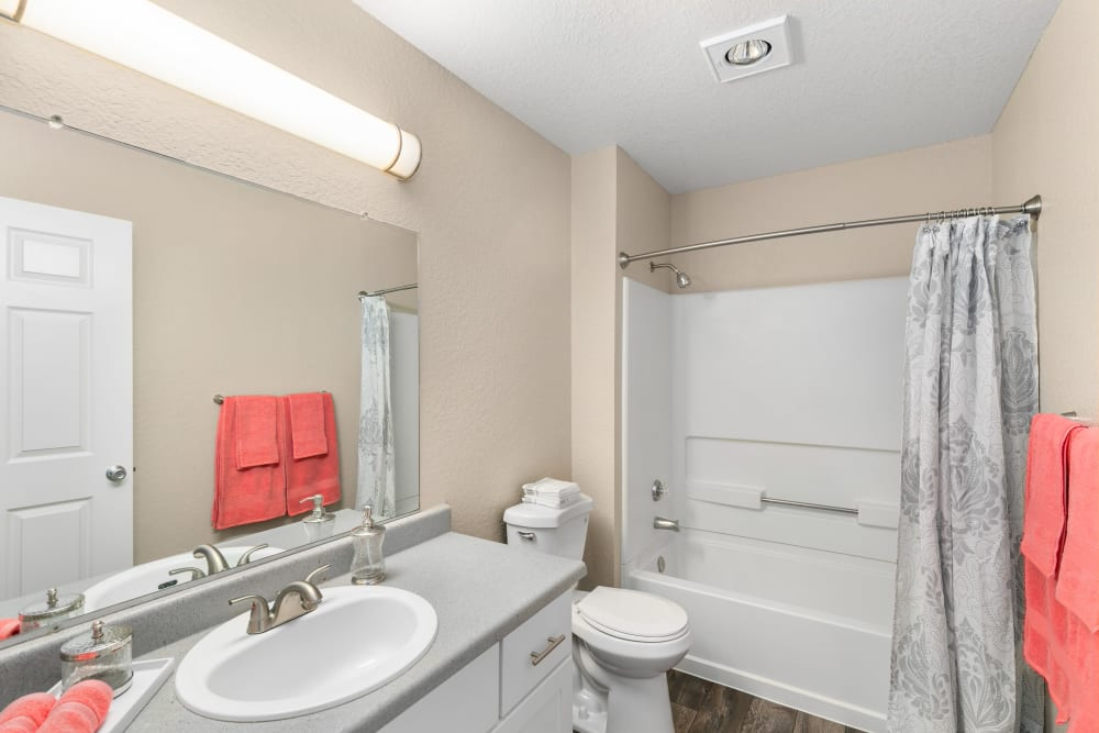 Updated bathroom with a large mirror and white cabinets at Carriage Park Apartments in Vancouver, Washington