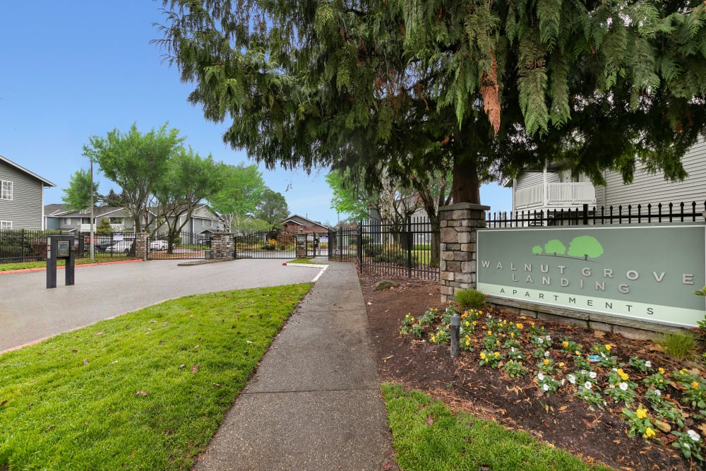 A walkway in front of the monument sign at Walnut Grove Landing Apartments in Vancouver, Washington
