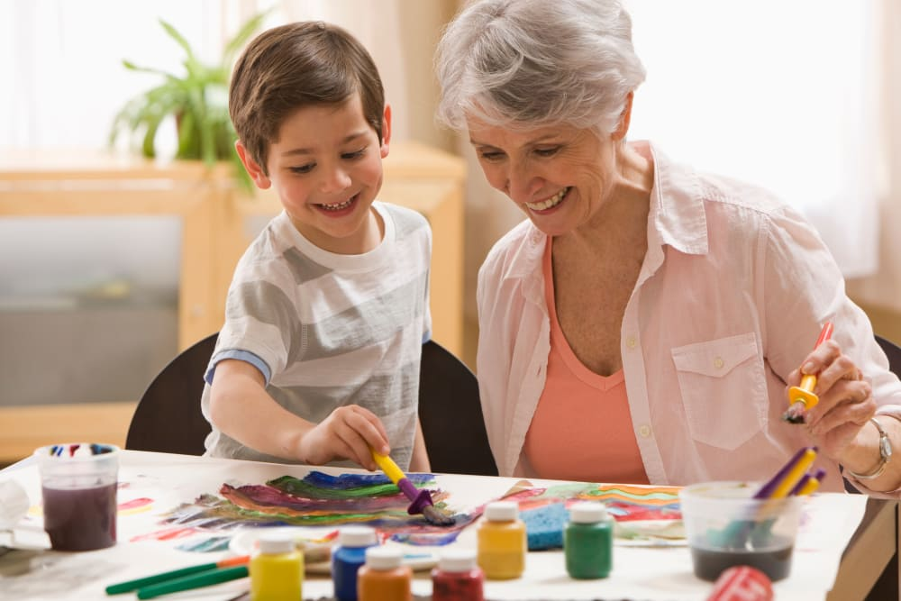 Happy resident painting with grandchild at Merrill Gardens at Rolling Hills Estates in Rolling Hills Estates, California