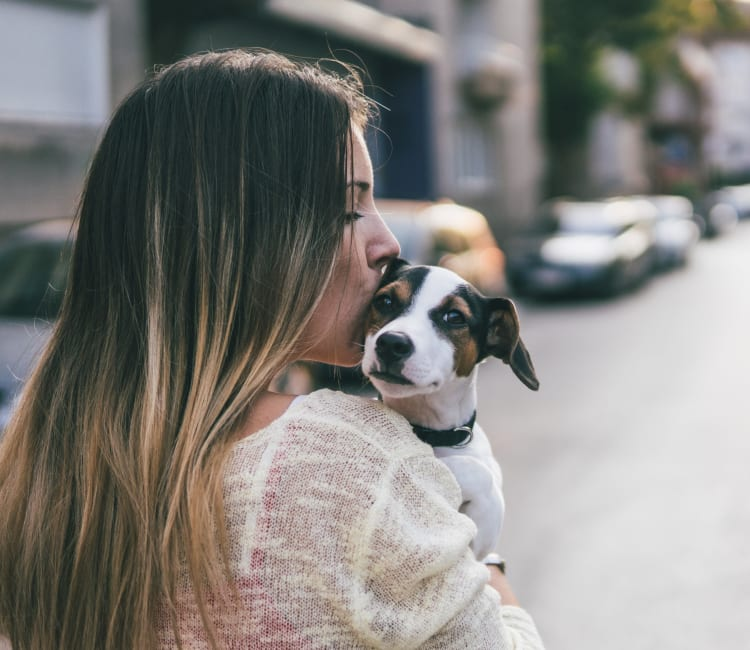 Resident giving her puppy a kiss outside their new home at Sofi Westview in San Diego, California