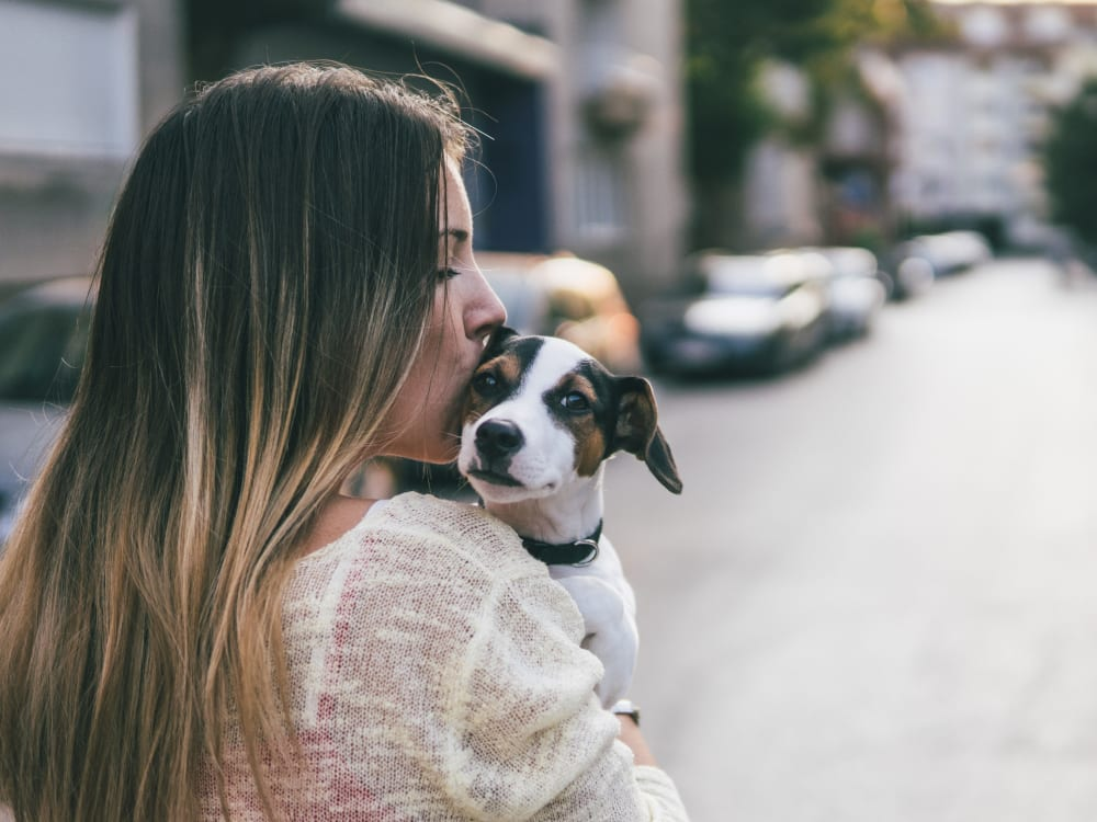 Resident giving her puppy a kiss outside their new home at Haven Martinez in Martinez, California