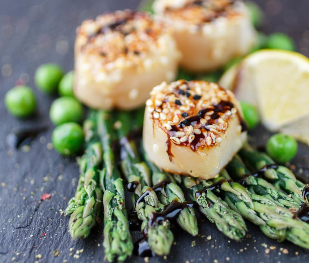 Delectable scallops and asparagus dish prepared at a restaurant near Sofi at 3rd in Long Beach, California