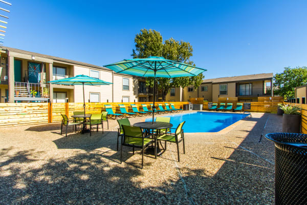 Swimming pool and patio furniture at Sausalito Apartments in College Station, Texas